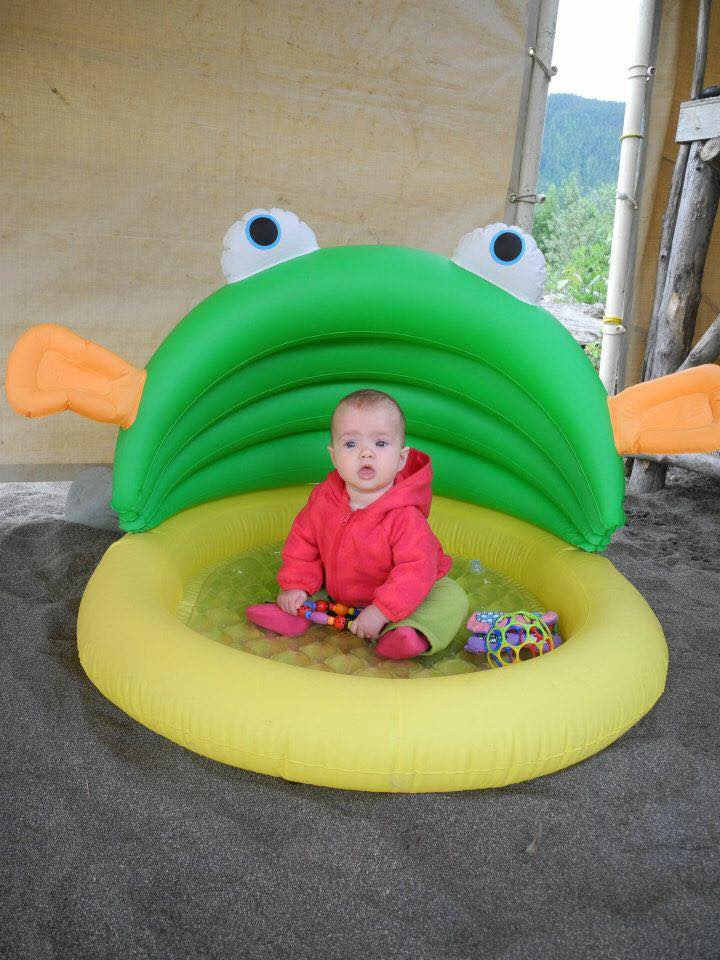 baby sitting in inflatable pool for camping