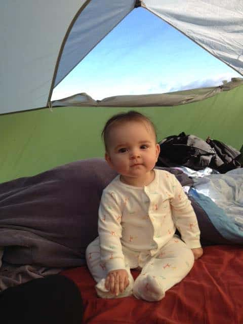 baby in pajamas sitting in tent