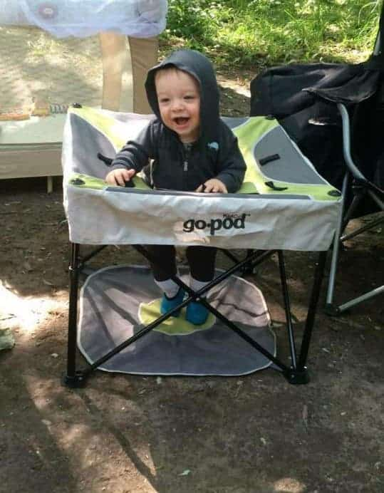 baby in portable play area while camping