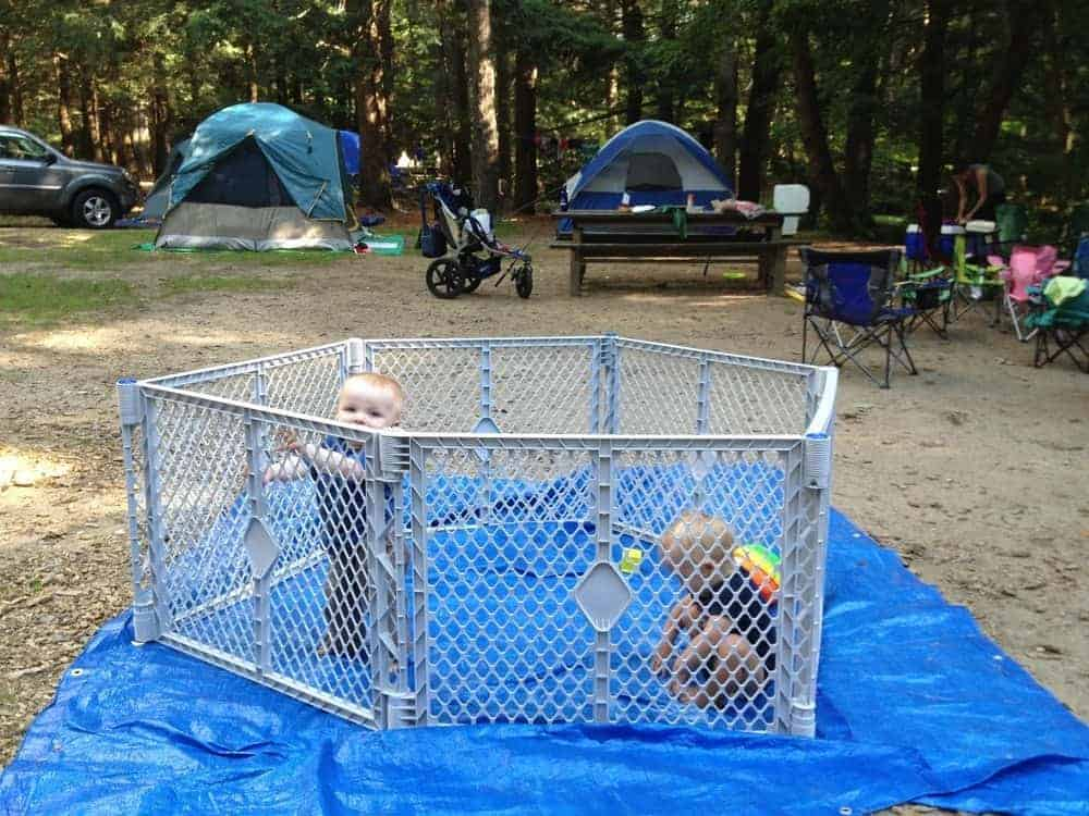 babies playing in playard camping with tarp underneath