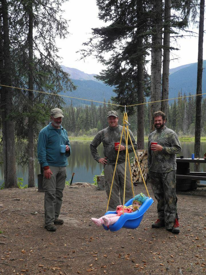 baby camping with swing attached to line three men in the background