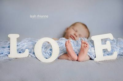 Baby laying on the floor with feet making the V in the word love