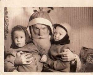 black and white creepy shot of father christmas with two kids