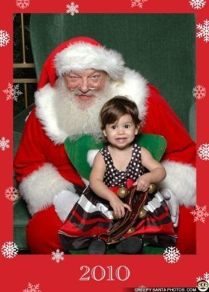 creepy santa with little girl sitting on his lap in a photo