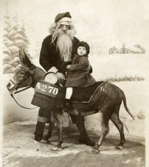 old time saint nick image with a child and a donkey
