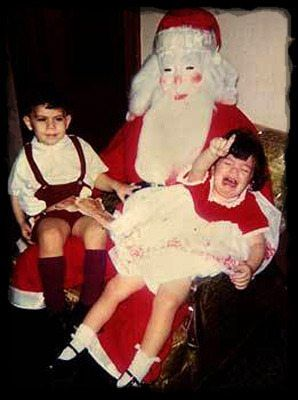 little girl crying on santa's lap with little boy sitting next to her