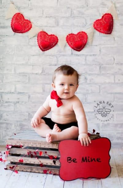 Baby surrounded by heart decor holding sign that says be mine