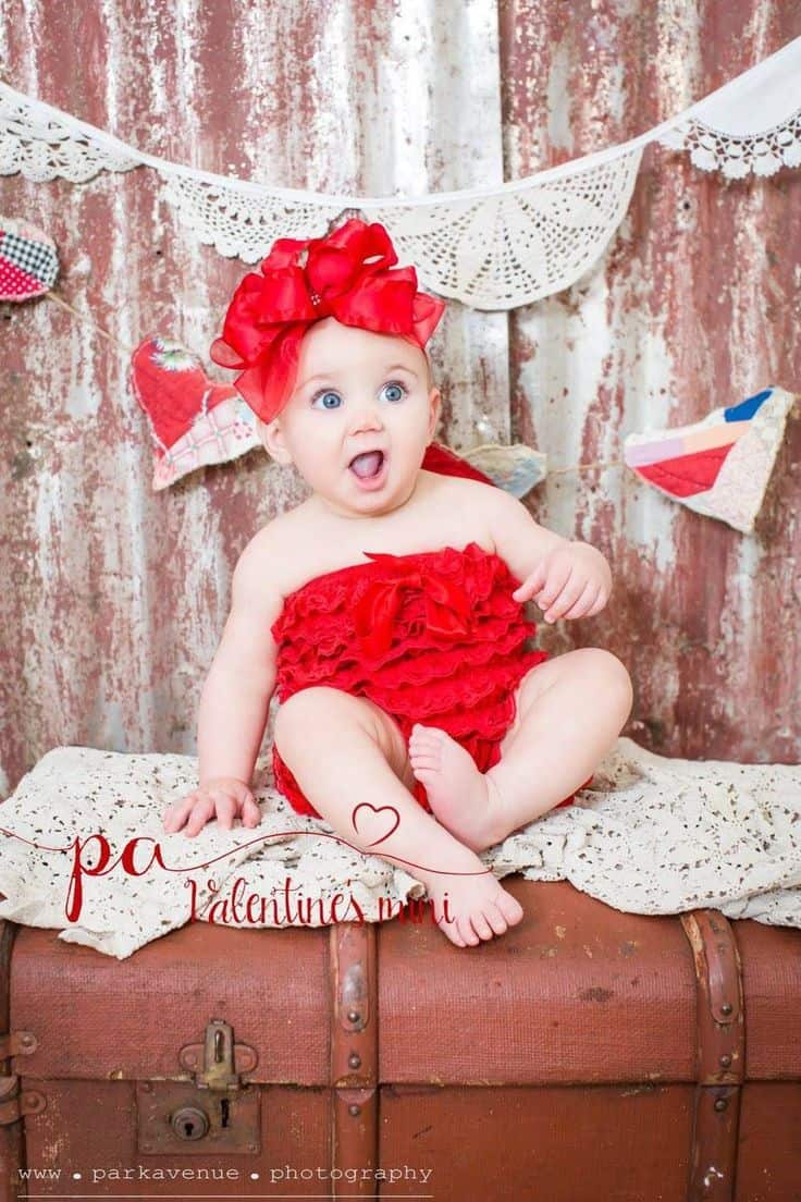 Baby making surprised face wearing red outfit with giant red bow