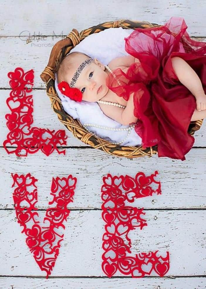 Baby laying in basket wearing red tutu with word Love spelled out