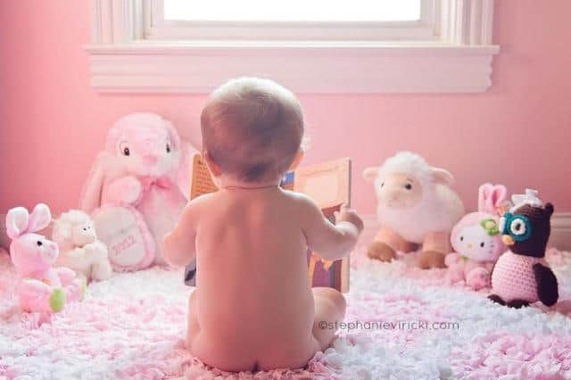 Baby sitting in bedroom reading book to stuffed animals