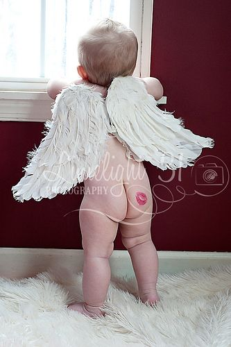 Baby looking out window with angel wings on and lip stick kiss mark on their bottom