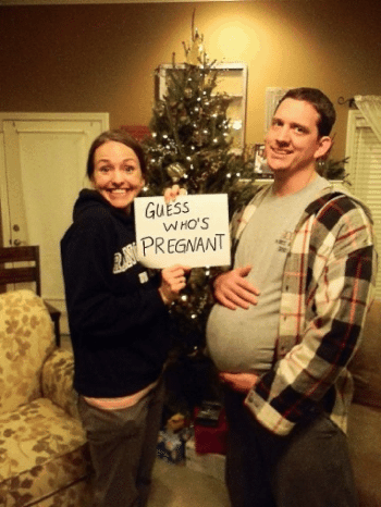 woman holding guess who's pregnant sign with fake bump on dad fun pregnancy announcement