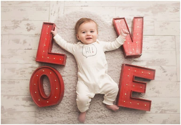 Baby laying on floor surrounded by the letters L O V and E - Baby's First Valentine's Day Photo shoot