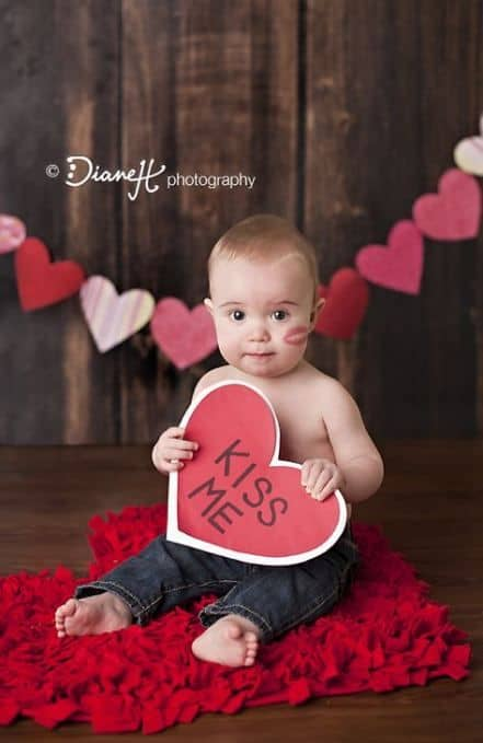 baby sitting on heart shaped rug on the floor holding a kiss me sign - Baby's First Valentine's Day Photo shoot