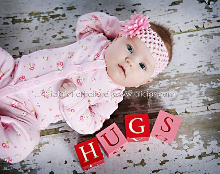 Baby laying on floor next to pink and red blocks spelling out Hugs
