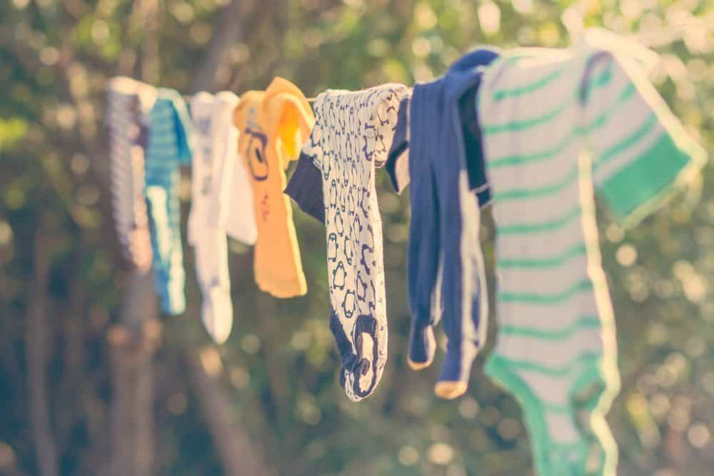 baby clothes hanging in the sun on a line