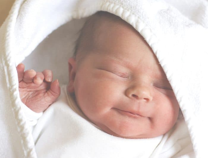 newborn baby wrapped up in a white blanket