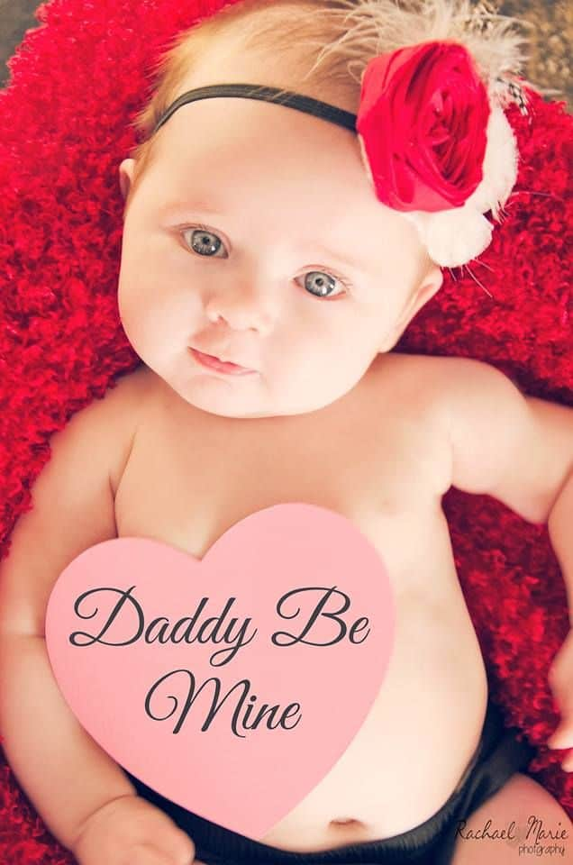 Baby with red flower headband and Daddy Be Mine heart note on their tummy - Baby's First Valentine's Day Photo shoot