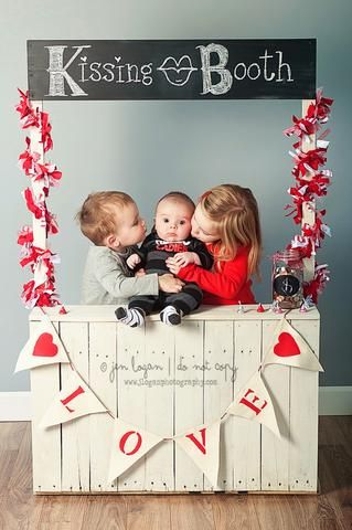 Two older siblings kissing baby brother on both of his cheeks