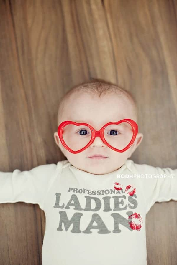 Baby laying on floor wearing red heart shaped glasses