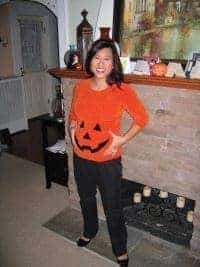Woman dressed in an orange shirt made into a DIY pumpkin maternity costume