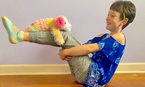 Young kid doing yoga with stuffed animal
