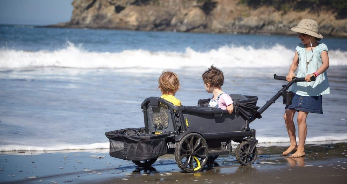 two kids sitting in a stroller wagon while girl pulls it on the beach
