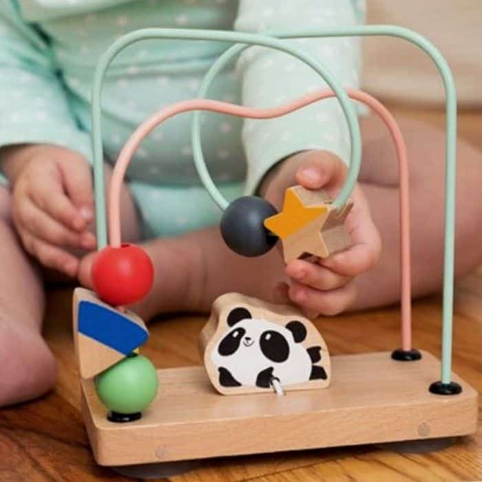 Baby playing with wire maze toy
