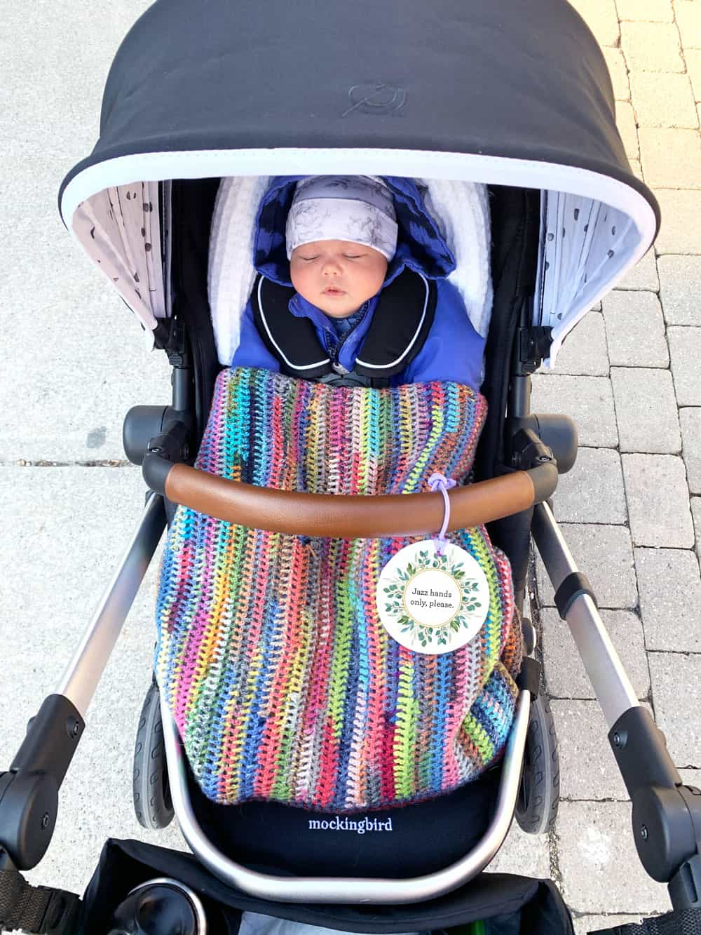 """Baby in stroller with a """"do not touch"""" stroller sign"""