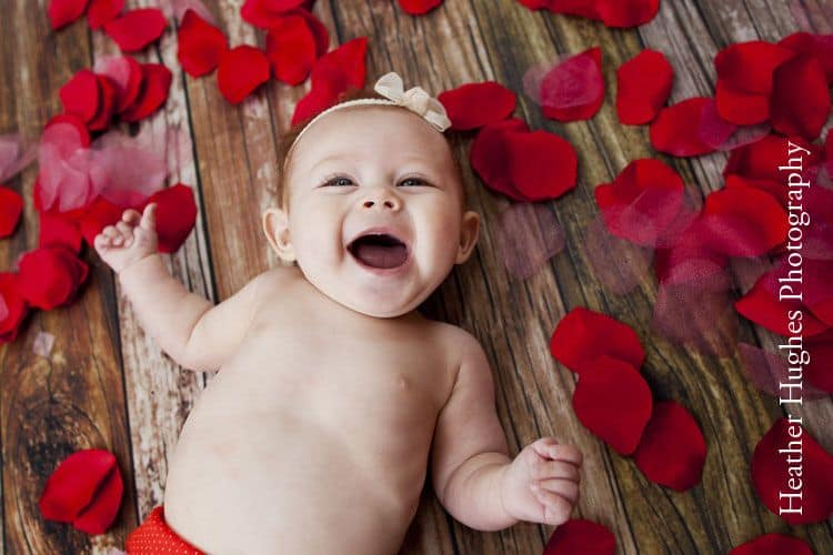 Laughing baby laying on floor surrounded by rose petals