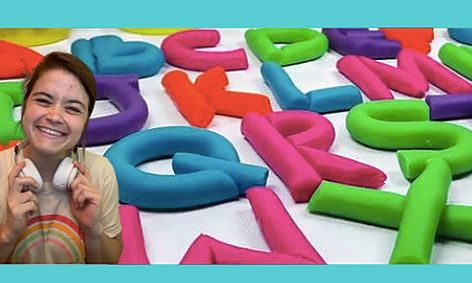 Woman smiling in front of play dough letter background