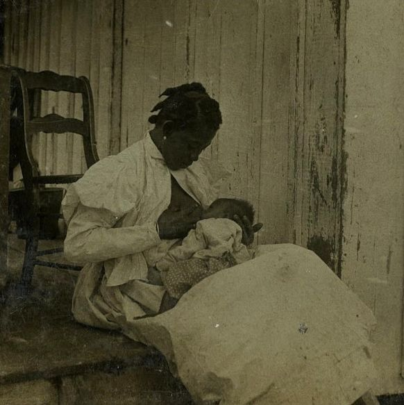 Black and white photograph of dark haired mother smiling down at nursing baby