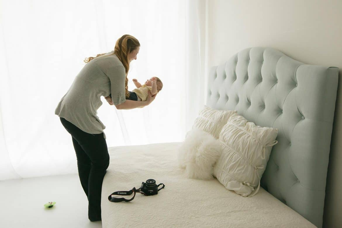 mom doing DIY baby photoshoot with her baby on the bed