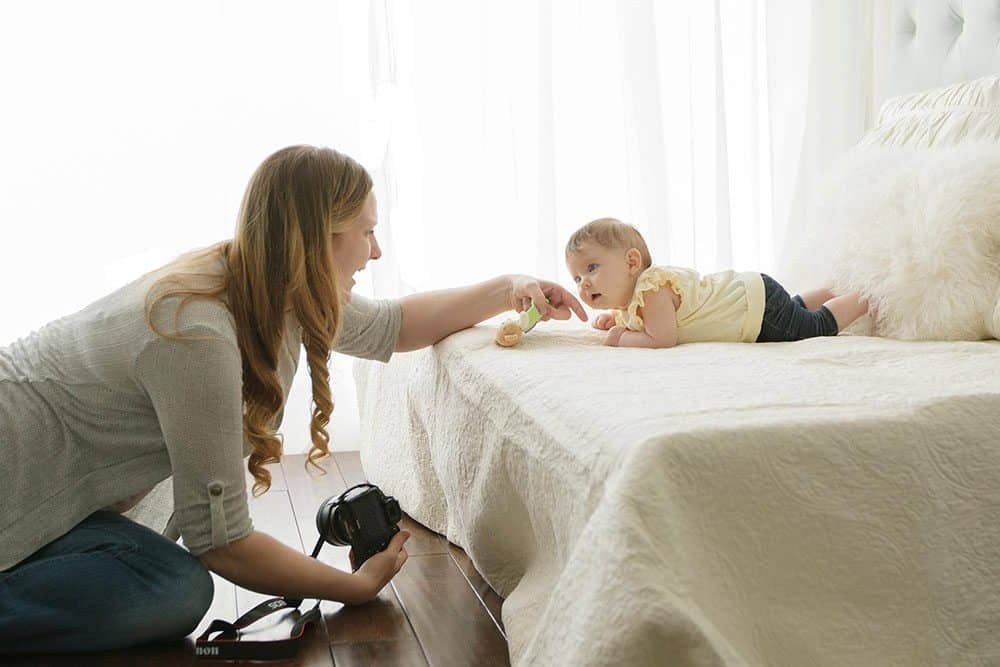 mom helping baby lift head for home photoshoot