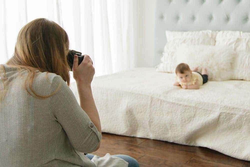 mom taking a picture of her baby on the bed in a DIY baby photoshoot