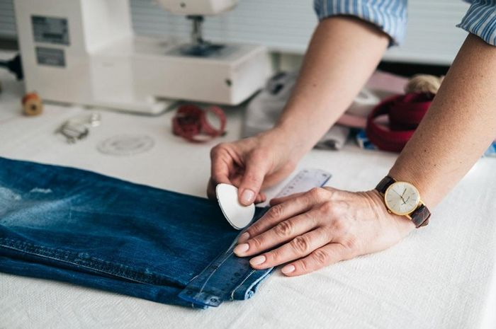 person altering the hem of jeans