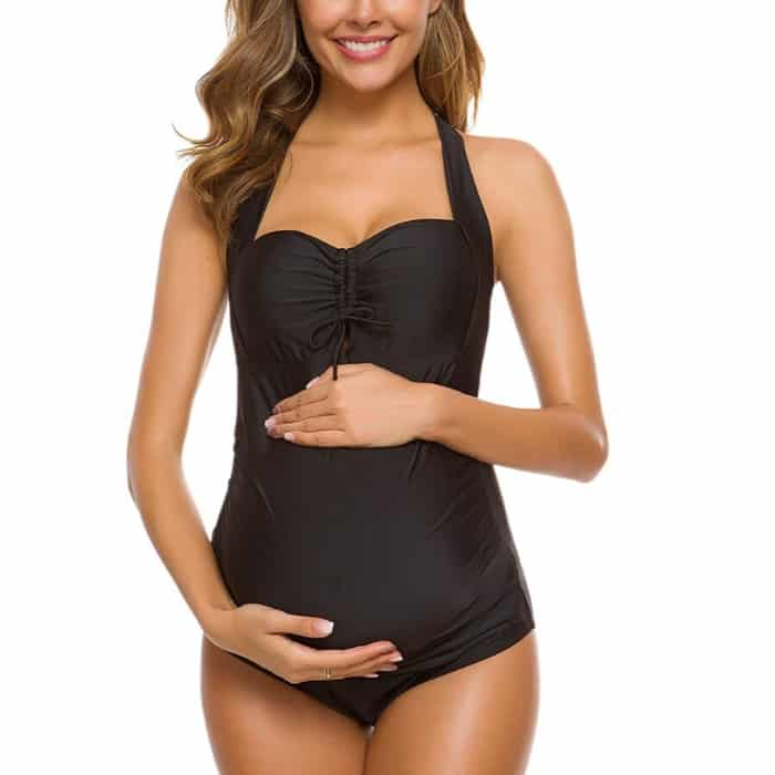 woman holding pregnancy bump in black inexpensive one piece swim suit
