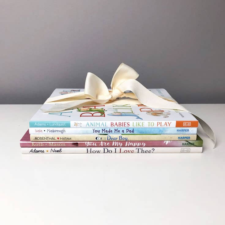stack of baby books with a bow