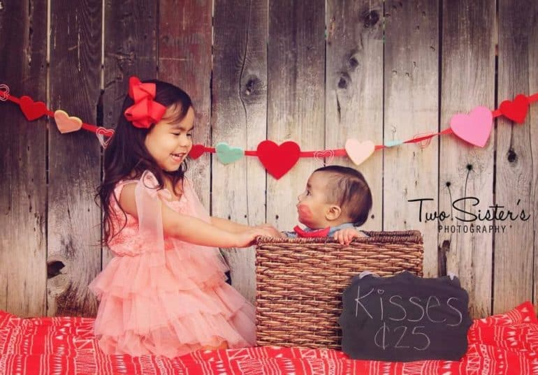 siblings sitting next to each other in homemade kissing booth Baby's First Valentine's Day Photo shoot