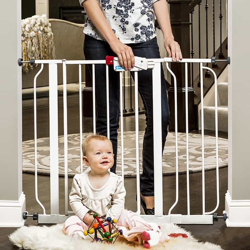 baby playing on one side of a baby gate - things to keep at grandma's house