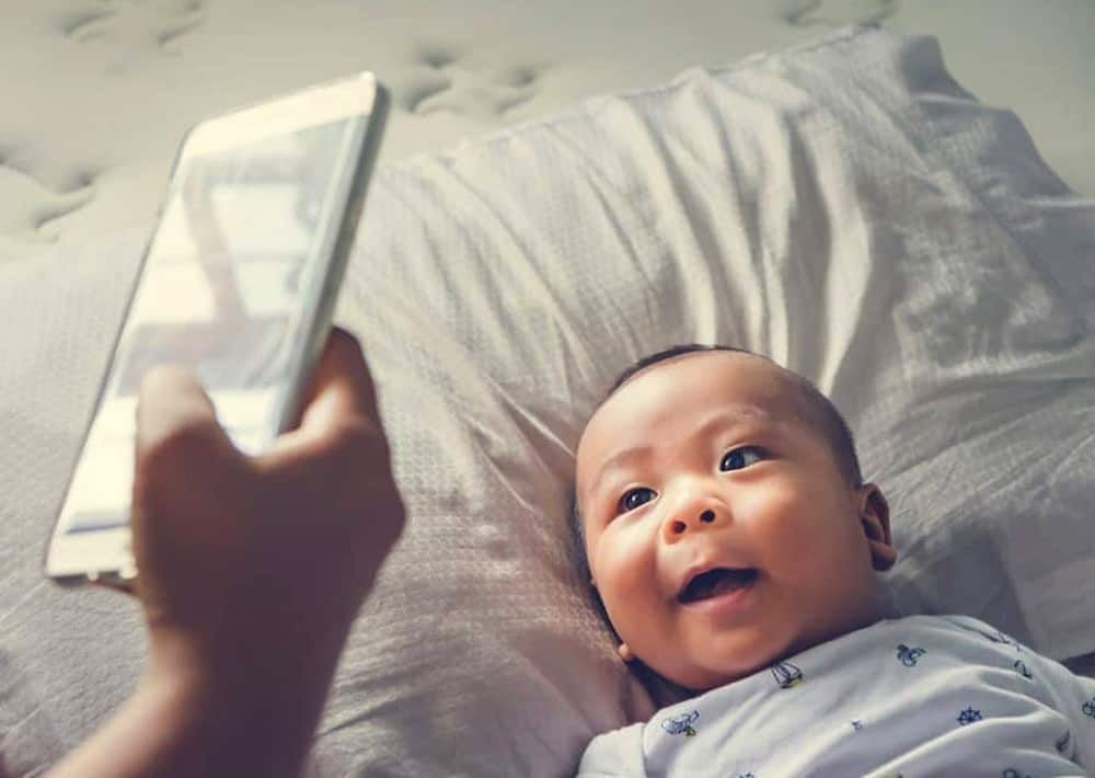 parent taking picture of baby with smart phone
