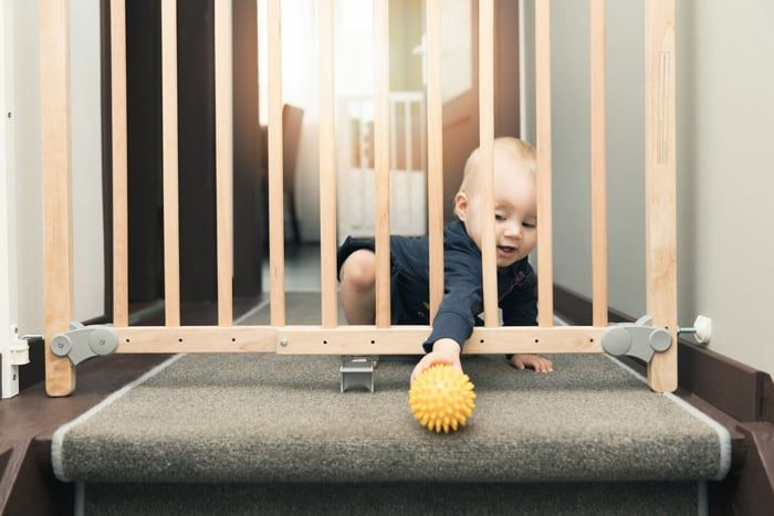 baby trying to grab yellow ball through safety gate at the top of the stairs.
