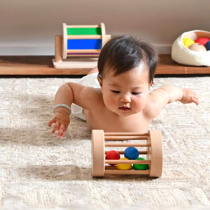 baby looking at wooden toy in Montessori play nursery