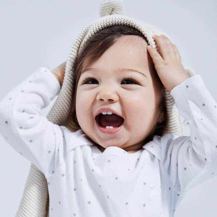 smiling baby wearing white organic baby clothes with bear sweater