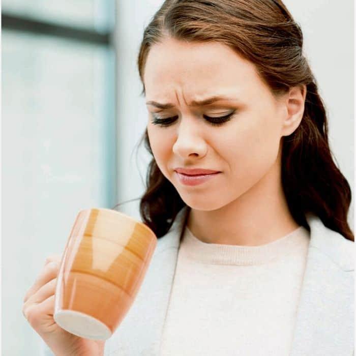 woman finds drink in mug tastes sour