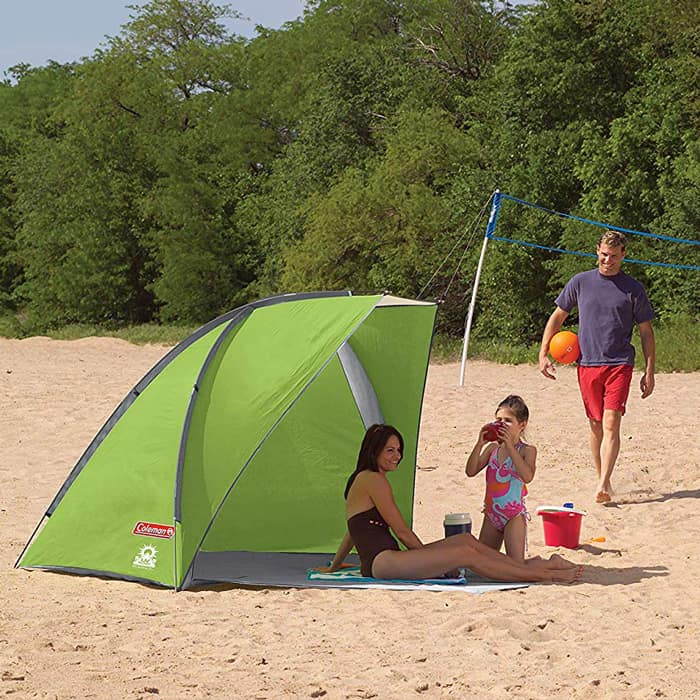 family sitting in coleman beach tent on the beach