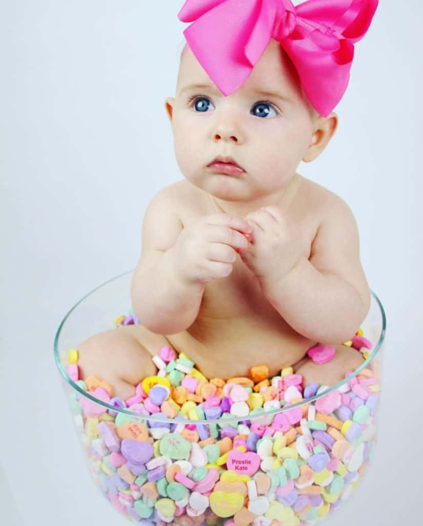 Baby sitting in bowl of Sweat Hearts with large pink bow on head