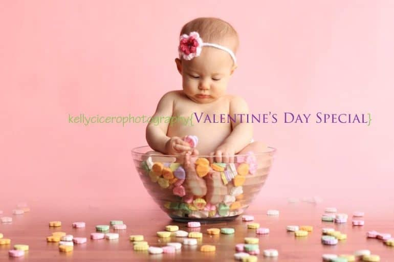 Baby sitting in bowl of Sweat Hearts with knitted flower headband on - Baby's First Valentine's Day Photo shoot