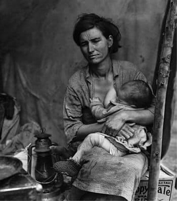 Black and white photograph of mother breastfeeding baby