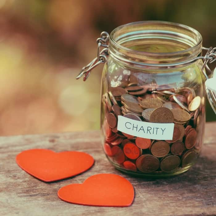 jar full of coins that says 'charity'